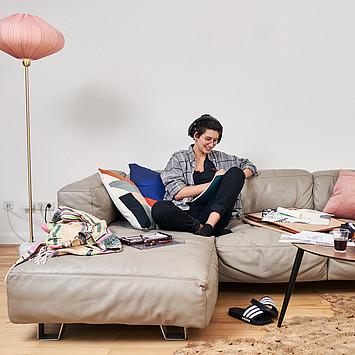 Eine junge hippe Frau hört Musik auf einem Sofa.